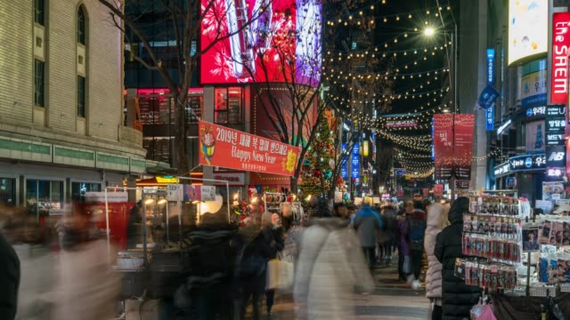 Timelapse people traveling with happiness and shopping in Myeongdong street market at Seoul, South Korea. Myeong Dong district is the most popular shopping market at Seoul city.