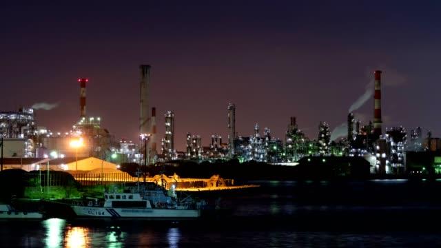 stockvideo's en b-roll-footage met 4k time-lapse: petrochemische plant olieraffinaderij met rook stack. tilt down shot - industriëel gebouw