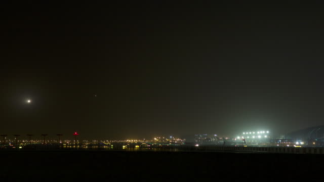 Timelapse planes land on runway and taxi to terminal at airport at night, Dubai