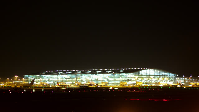 Timelapse planes taxi outside Terminal 5 at night, Heathrow, London, UK