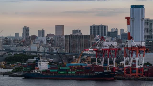 vídeos de stock, filmes e b-roll de time-lapse: vista aérea de trabalho portuário com navio de carga e recipiente no por do sol de japão da baía de tokyo - recipiente