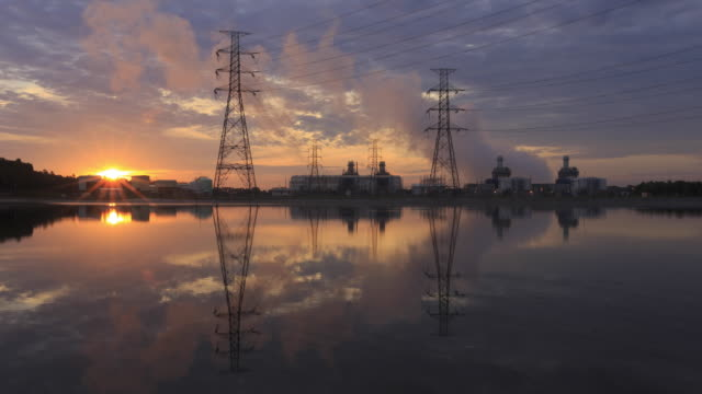 Time-lapse pylons near power transform station at sunrise
