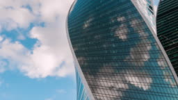 Timelapse - reflection of moving white clouds in glass wall of modern skyscraper