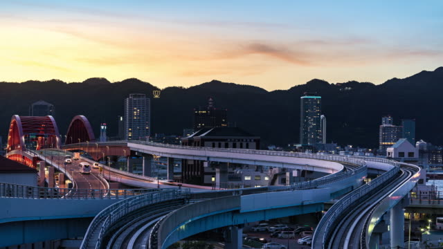 time-lapse: road and railroad transportation to kobe cityscape in hyogo kansai japan at sunset twilight night - elevated train stock videos & royalty-free footage