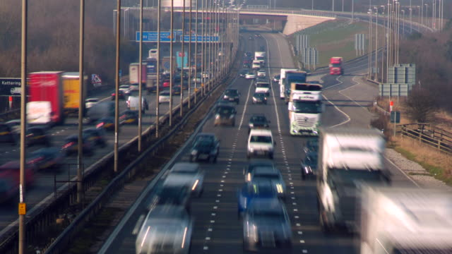 timelapse, road transport. tilt down to fast moving traffic on the m1 motorway at the busy m6 junction.  - road marking stock videos & royalty-free footage