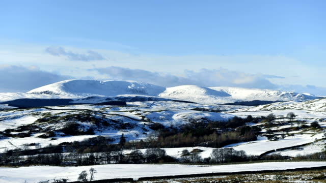 Timelapse rural winter scene with snow covered hills and fields