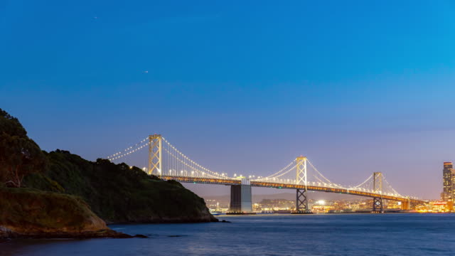 vídeos de stock e filmes b-roll de time-lapse san francisco bay bridge at dusk from treasure island, california, sunset, usa - san francisco oakland bay bridge