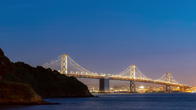 time-lapse san francisco bay bridge at dusk from treasure island, california, sunset, usa - san francisco oakland bay bridge stock videos and b-roll footage