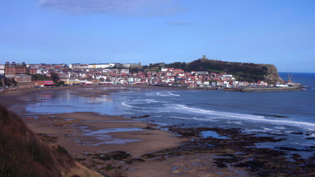 Timelapse, Scarborough South Bay and deserted beach with the sea front, town and castle on the skyline in winter sunshine