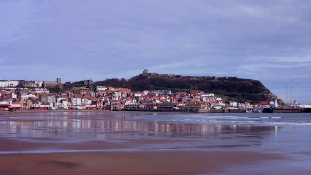 stockvideo's en b-roll-footage met timelapse, scarborough south bay and deserted beach with the sea front, town and castle on the skyline in winter sunshine - scarborough engeland
