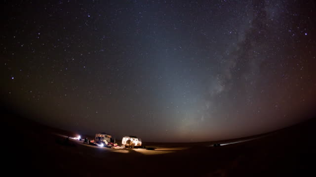 Timelapse, scenic night sky over snowy campsite