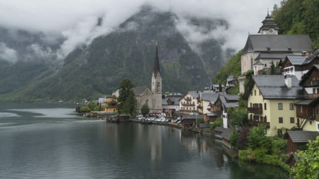 timelapse scenic view of famous hallstatt mountain village and boat port on a rainy day in summer covering much cloudy.  one of the travel destinations in austrian culture and the european alps and lakeshore in europe. - austrian culture stock videos & royalty-free footage