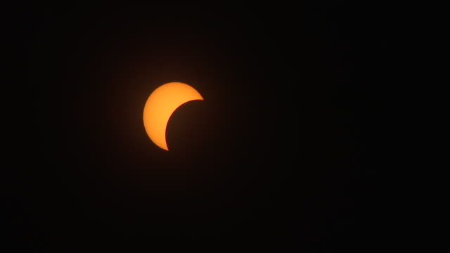 vídeos y material grabado en eventos de stock de clouds periodically race past the sun at 50% totality in the new york city metro during the august 21st 2017 great american eclipse a few sunspots... - mancha solar