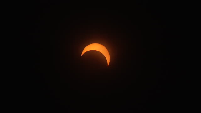 vídeos y material grabado en eventos de stock de clouds periodically race past the sun at the peak of 71% totality in the new york city metro during the august 21st 2017 great american eclipse - mancha solar