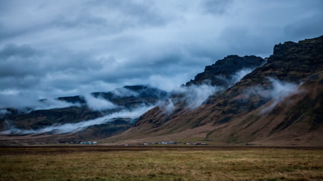 Time-lapse sequence showing, first, white clouds rolling onto squat, knobbly mountains, then water flowing from Jökulsárlón glacier lagoon under a suspension bridge, Iceland.