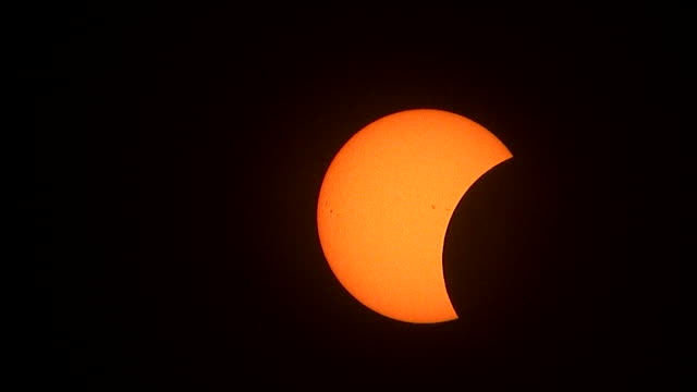 vídeos y material grabado en eventos de stock de the sun at around 25% totality slides across the frame from top left to bottom right as sunspots slowly disappear from the sun's disc as the moon... - mancha solar