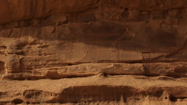 vídeos de stock, filmes e b-roll de timelapse shadows shift over rock and petroglyphs, wadi rum, jordan - exposto ao tempo
