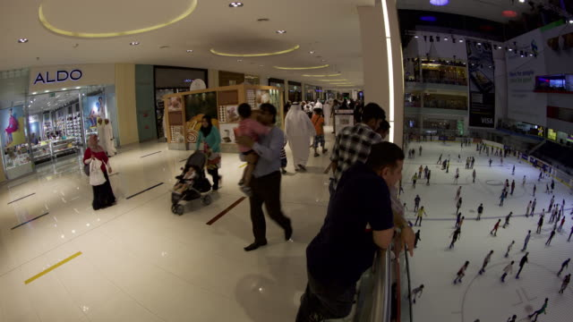 timelapse shoppers and ice skaters on ice rink, dubai mall, dubai - clothes shop stock videos & royalty-free footage