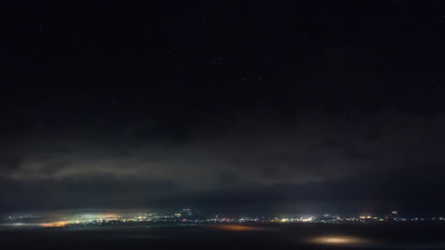 Time-lapse shot: Neon lights reflected off the sea of clouds over the Aso Caldera, Kumamoto, Japan.