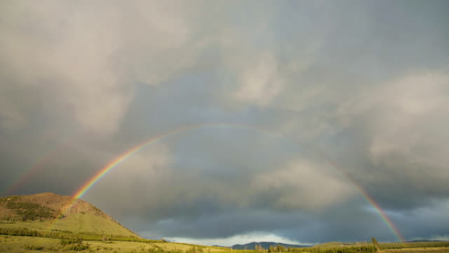 timelapse shot of a rainbow appearing over the meadow - rainbow stock videos & royalty-free footage
