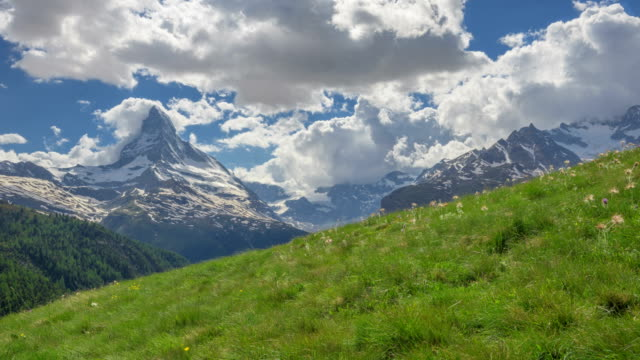 time-lapse shot of alps mountain and grass field taken from sunnegga area (popular travel destination) of switzerland - alps stock videos and b-roll footage