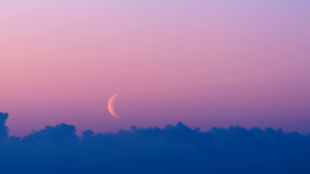 time-lapse shot of crescent moon on pink white night sky over the landscape of iceland - halvmåne form bildbanksvideor och videomaterial från bakom kulisserna