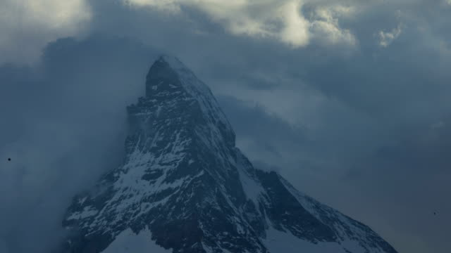 Time-Lapse shot of Matterhorn (one of the highest summits in Alps) surrounded by dark cloud sea like fog