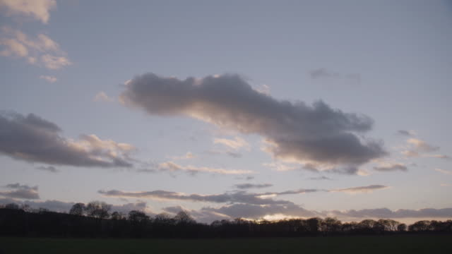 timelapse shot of moving clouds over the field at sunset - nature stock videos & royalty-free footage