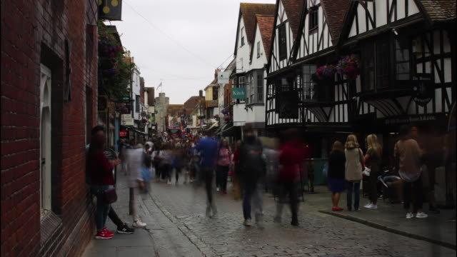 Timelapse shot of pedestrians on Canterbury's historic High Street leading to Westgate, Kent, UK.