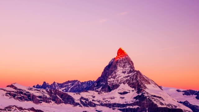 Time-Lapse shot of red sun light lying on Matterhorn (one of the highest summits in Alps)