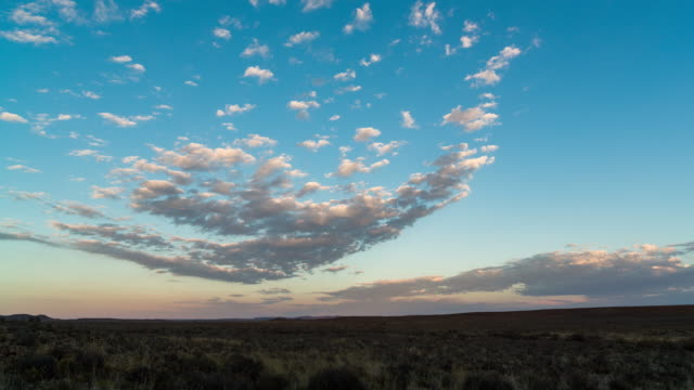 timelapse shot of slow moving scattered clouds at sunrise over a karoo landscape - karoo bildbanksvideor och videomaterial från bakom kulisserna