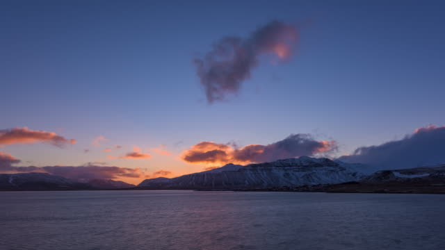 Time-Lapse shot of Snowy Mountain in Iceland over lake at dawn
