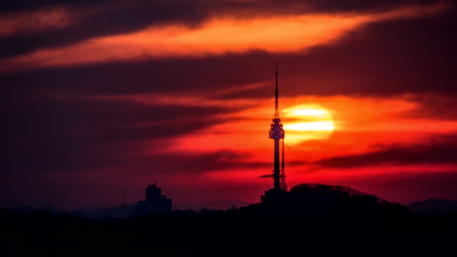 Time-Lapse shot of sun setting over N Seoul Tower (also called Namsan Tower and it is Land Mark of Seoul) on dramatic red sky