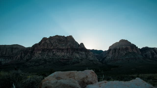 timelapse shot of the sun rising over the mountains at the nevada desert with lens flare - nevada stock-videos und b-roll-filmmaterial