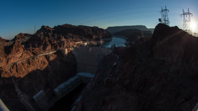 timelapse shot of the sunrise over the hoover dam in nevada with lens flare - hoover staudamm stock-videos und b-roll-filmmaterial