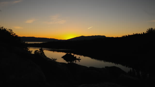 timelapse shot of the sunrise seen over emerald bay and nevada desert with lens flare - nevada stock-videos und b-roll-filmmaterial