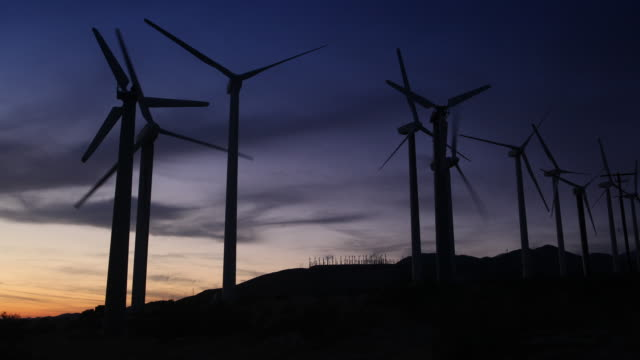 vídeos de stock, filmes e b-roll de timelapse shot of wind turbines on a hill in california, they turn as the sun sets. in the distance we can see another farm of windmills. beautiful cloud formations pass overhead. - rodando