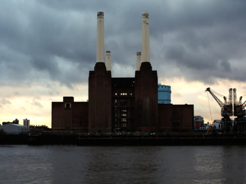 timelapse shot showing a front-on view of battersea power station. a barge shoots past on the thames. london, uk - battersea stock videos & royalty-free footage