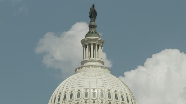 timelapse shot showing clouds moving behind the united states capitol building's dome and statue of freedom on a sunny day, washington, d.c., usa. - us senat stock-videos und b-roll-filmmaterial