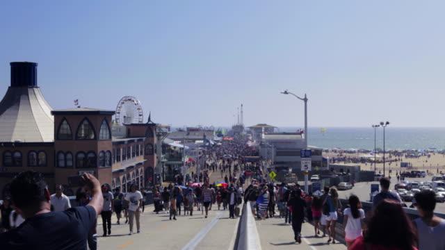 timelapse shows bustling river of humanity moving along walkway towards santa monica pier. - santa monica pier stock videos & royalty-free footage
