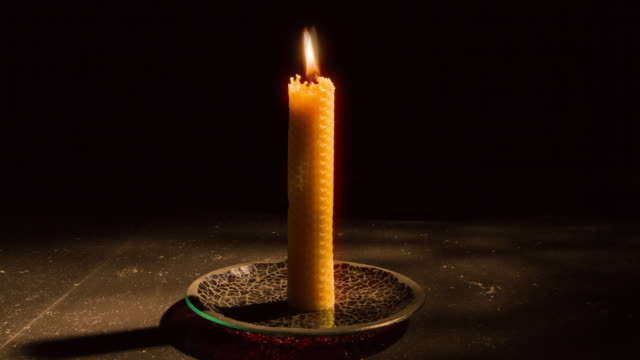 Time-Lapse Single candle burning down as camera tracks in  to close up