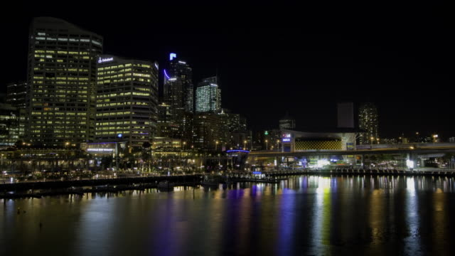 Time-lapse skyline at water's edge at Darling Harbour at night