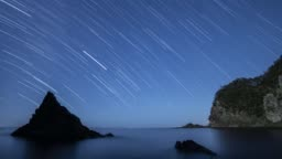 Timelapse star trail footage of the night sky over sea rocks, Izu Peninsula, Japan