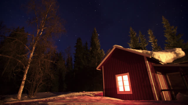Timelapse stars drift over snowy forest cabin at night, Sweden