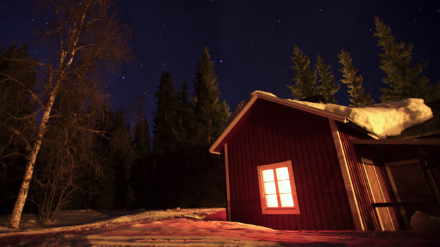 Timelapse stars drift over snowy forest cabin at night, Sweden