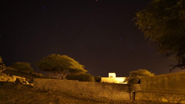 Timelapse stars drift over village, Dhofar, Oman