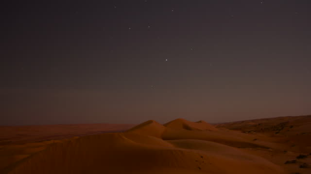 timelapse stars track over desert sand dunes and road at night, ibra, oman  - desert area stock videos & royalty-free footage