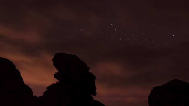 timelapse stars track over eroded rock stack in desert, wadi rum, jordan - stack rock stock videos and b-roll footage