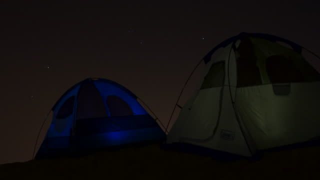 timelapse stars track over glowing tents in desert at night, uae - tent stock videos and b-roll footage