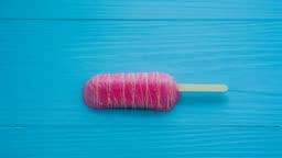 4K Time-lapse : Strawberry ice cream gradually melting on blue wooden table background.
